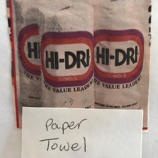 three packaged paper towels with sign