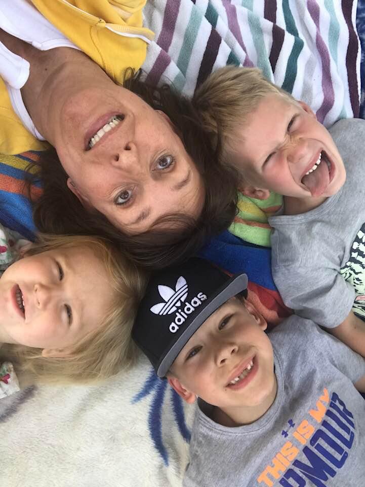 one woman three kids lying down all heads touching