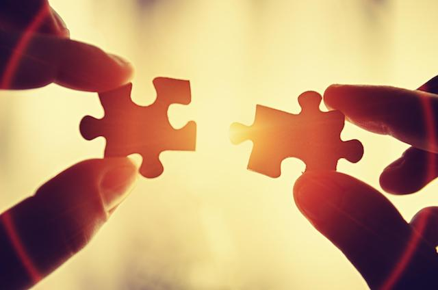 two hands putting together puzzle